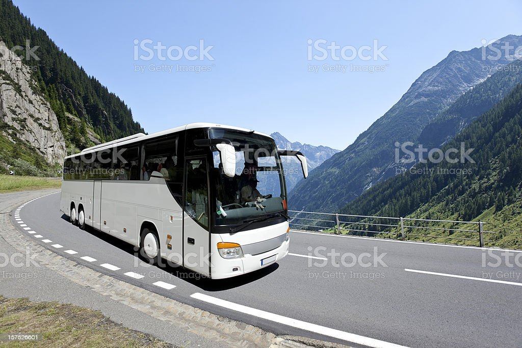 Blue sky over white bus crossing the alpes stock photo