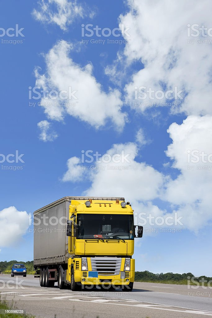 Blue sky over yellow truck on a highway royalty-free stock photo