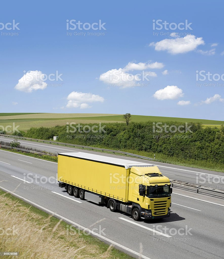 Blue sky over yellow truck on a highway stock photo