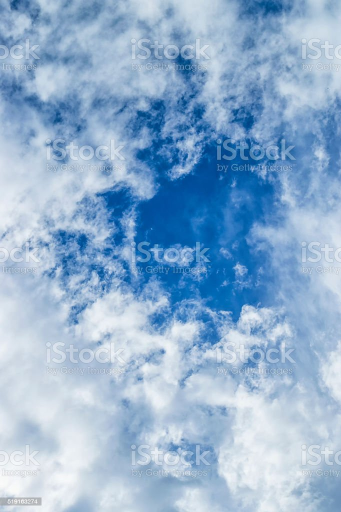 Blue sky showing as Altocumulus clouds break up stock photo