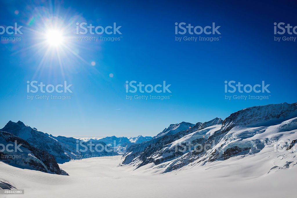 Blue sky sunburst above snowy winter mountain peaks Alps Switzerland stock photo