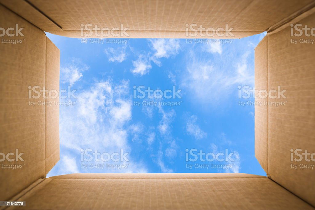 Blue sky viewed from inside of a cardboard box stock photo