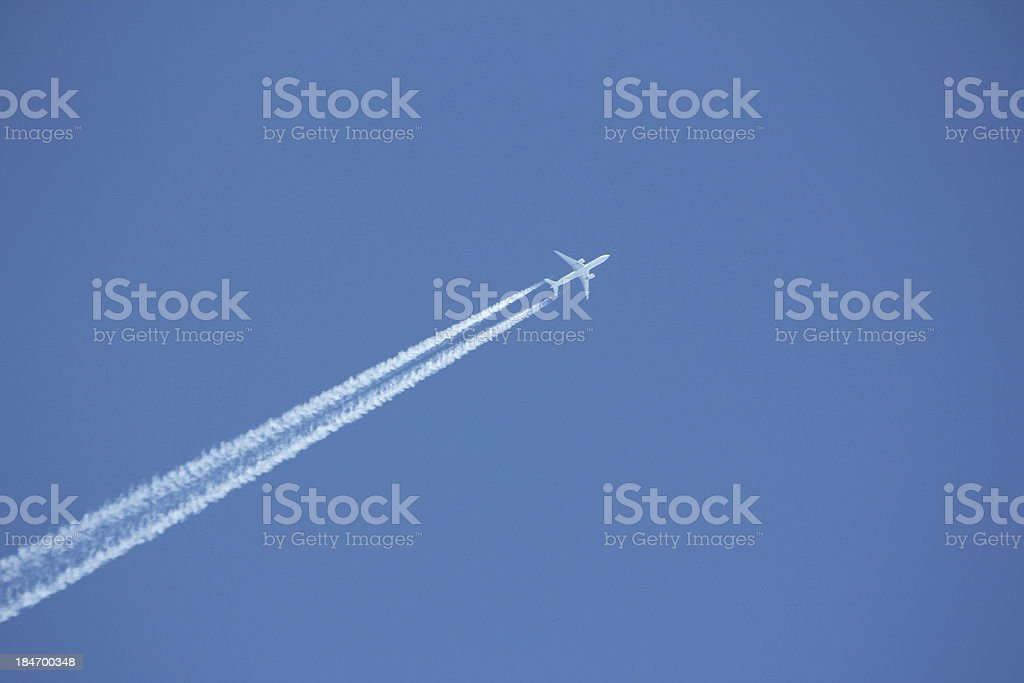 Blue Sky & White Condensation Trail of an Airplane stock photo