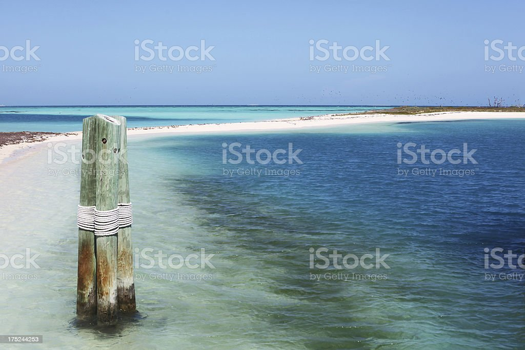 'Blue sky, white sand, turquoise water, pilings lashed together.' stock photo