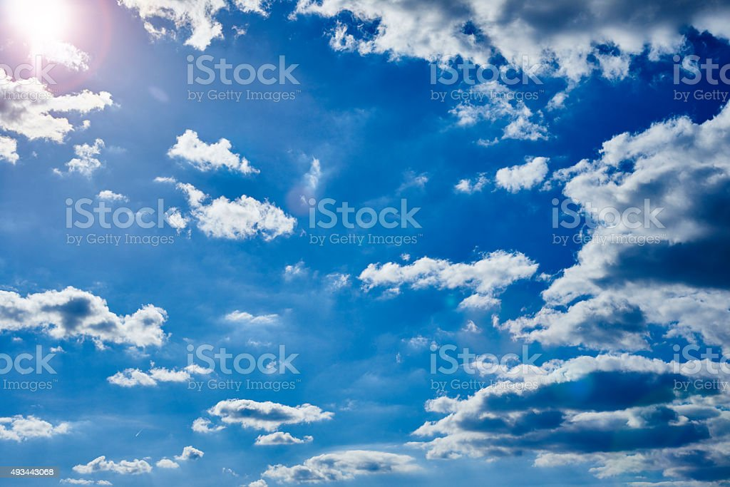 Blue sky with clouds and lens flare from the sun stock photo