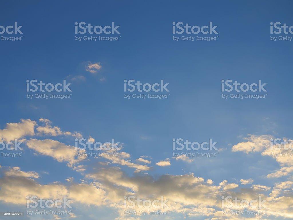 Céu azul com nuvens, iluminado ao pôr do sol foto de stock royalty-free