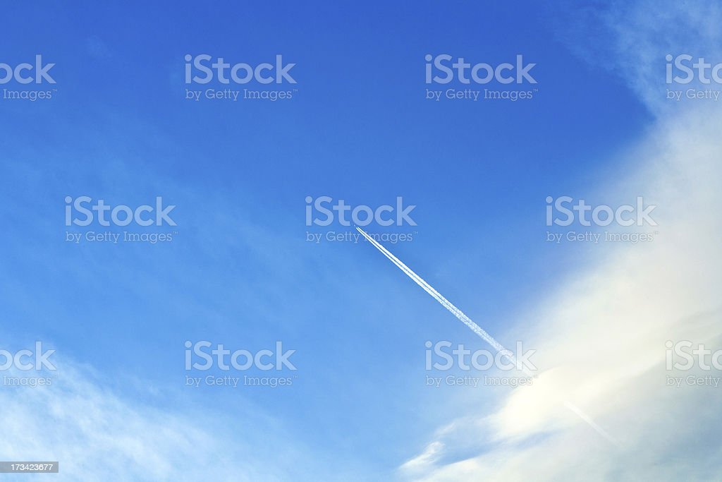 blue sky with condensation trail of an aircraft royalty-free stock photo