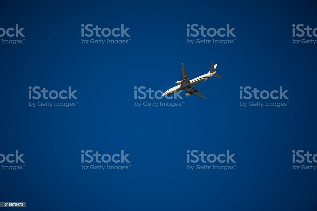 Blue sky with Jet Airplane flying across the middle stock photo