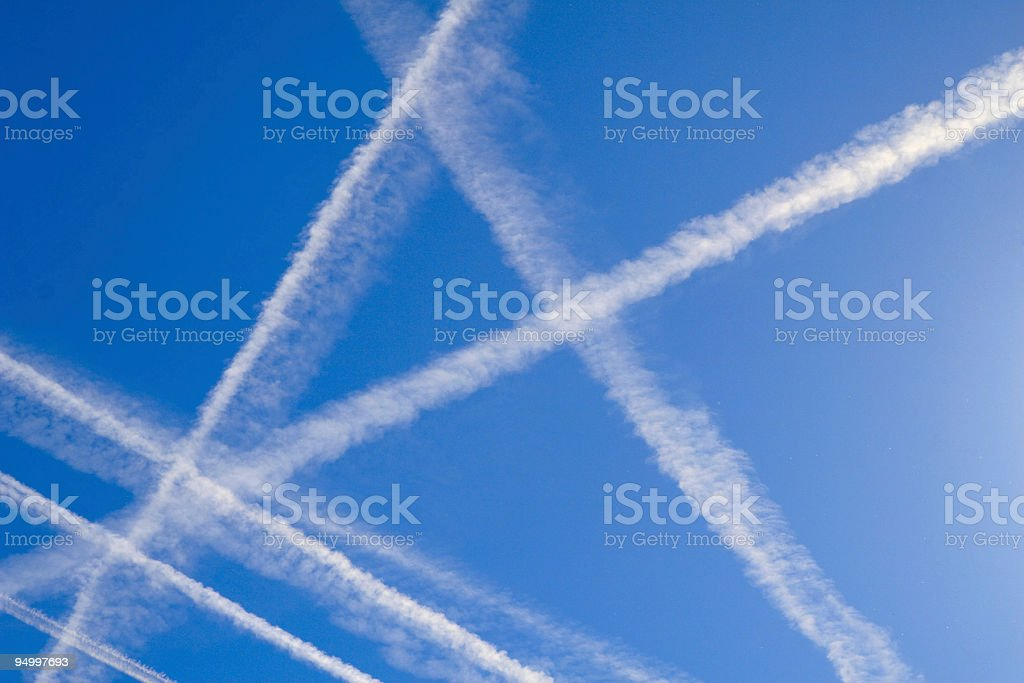 A blue sky with plane trails crossing over each other stock photo