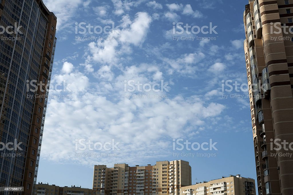 Blue sky with small clouds between homes royalty-free stock photo