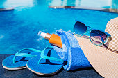Blue slippers with sunscreen cream, towel, straw hat and sunglas