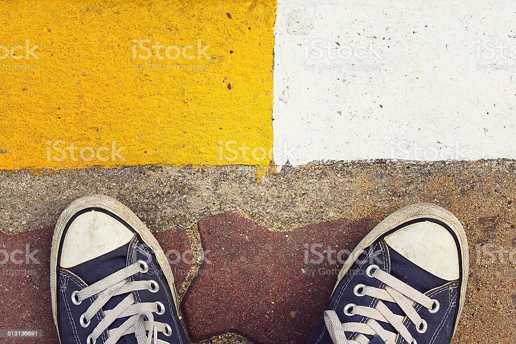 Blue sneakers from an aerial view on concrete block pavement. stock photo
