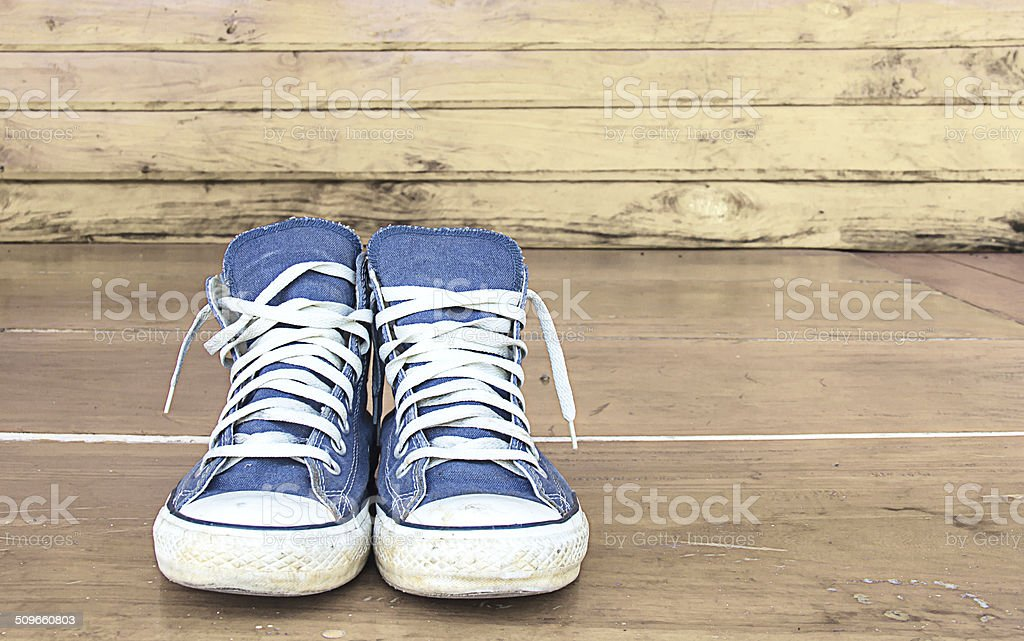 blue sneakers on the wooden floor, vintage stock photo