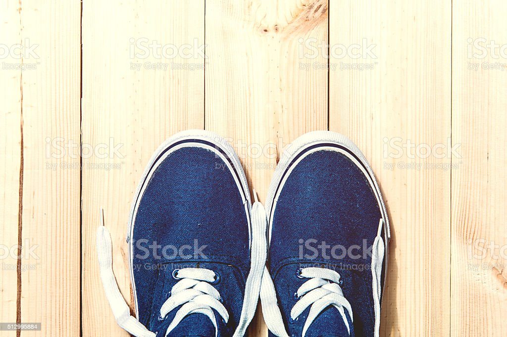 Blue sneakers on wooden background with copy space. Top view stock photo