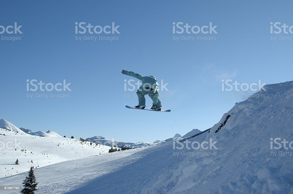 Blue snowboarder grabs during jump in mountains. Lots of copyspace. royalty-free stock photo