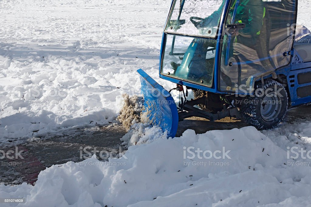 Blue snowplow removing snow stock photo