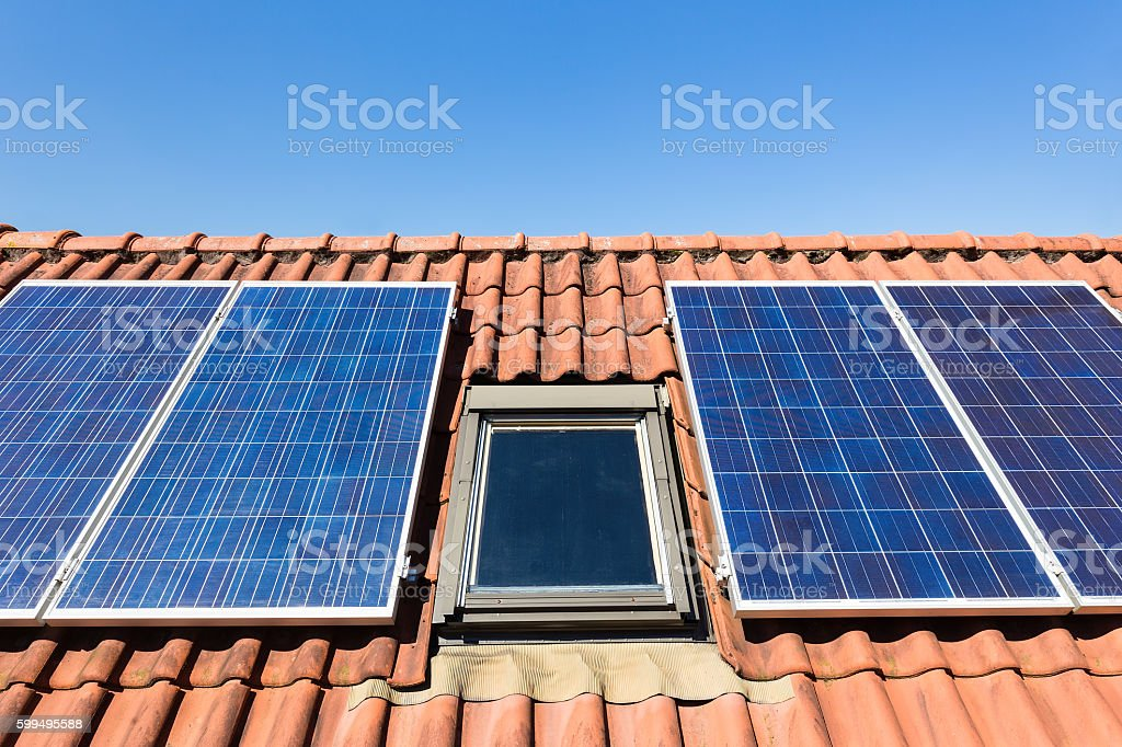 Blue solar collectors and attic window stock photo