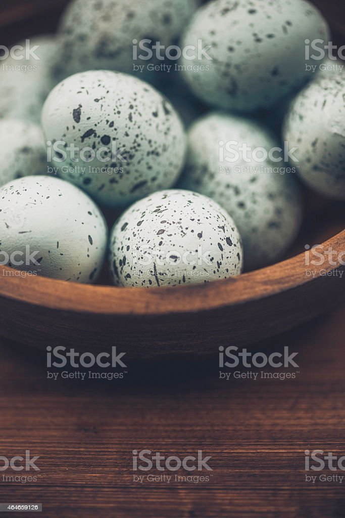 Blue speckled eggs in rustic bowl. Easter arrangement. stock photo