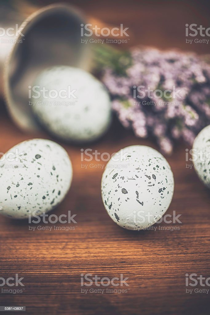 Blue speckled eggs, pewter egg cup and flowers. Easter arrangement. stock photo
