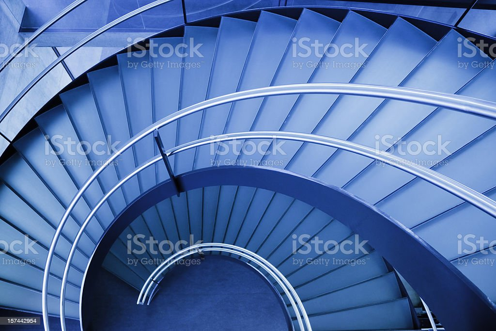 A blue spiral staircase seen from above stock photo