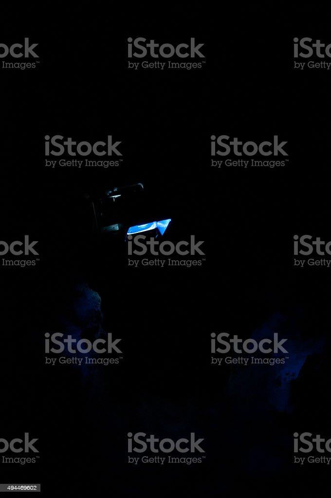 blue spotlight in dark cave stock photo
