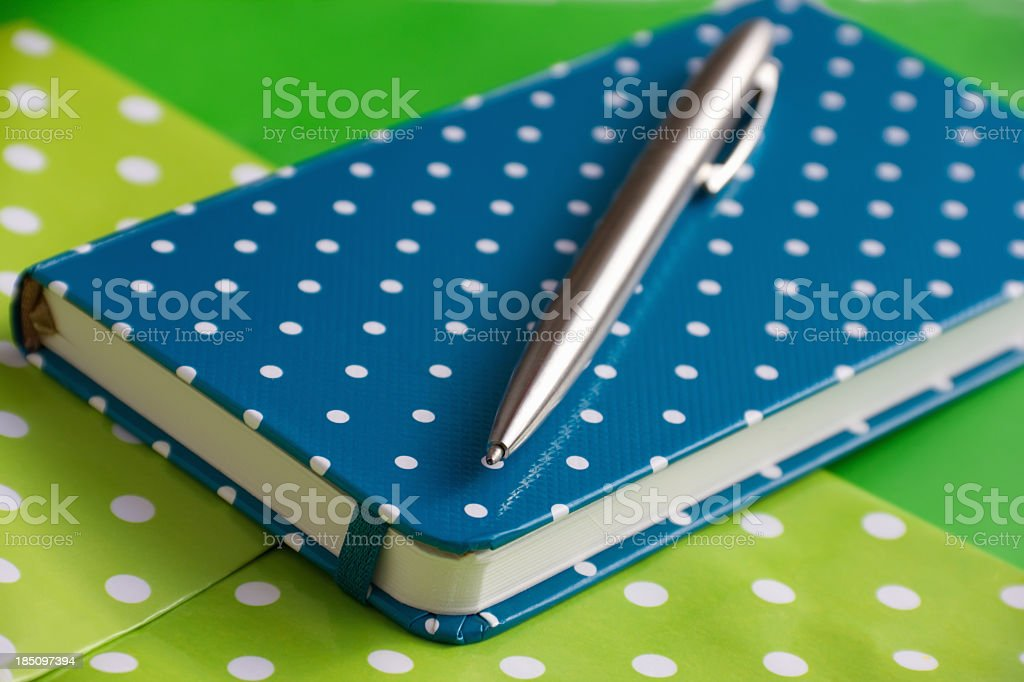 Blue spotted notebook and pen on green background stock photo
