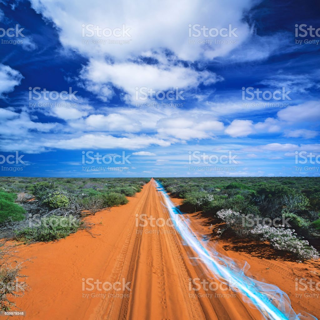Blue streak of light on dirt road against cloudy sky stock photo