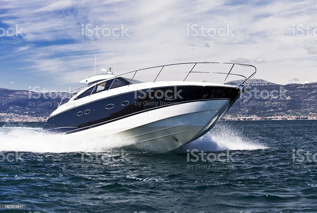 A blue striped white yacht speeding across the sea stock photo