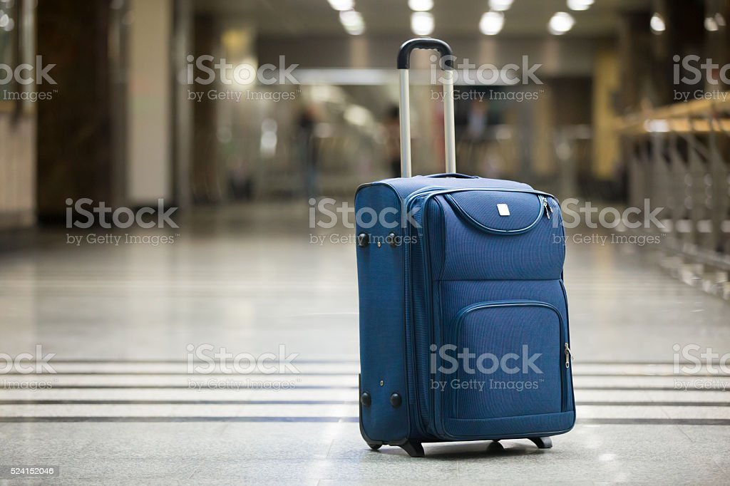 Blue suitcase at airport stock photo