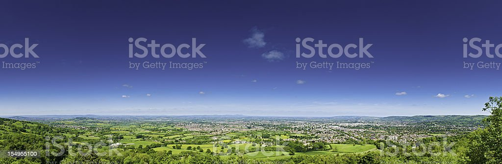 Blue summer skies over green patchwork landscape fields houses panorama stock photo