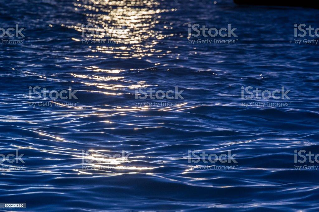 Blue sun reflection on sea background ripples stock photo