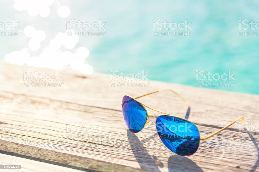 Blue Sunglasses on wooden decking by seaside stock photo