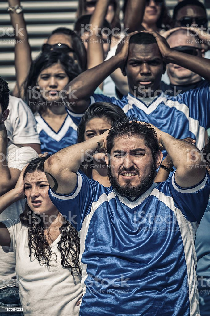 Blue supporting fans in dispair with their teaming losing (I) royalty-free stock photo