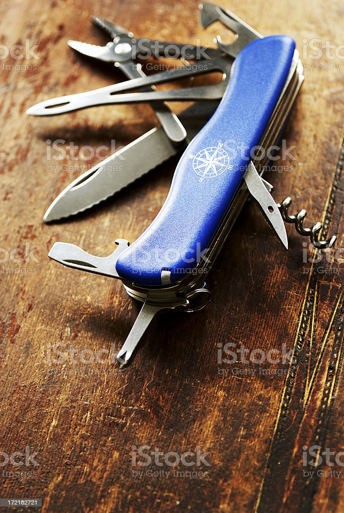 A blue Swiss Army knife on a wooden table stock photo