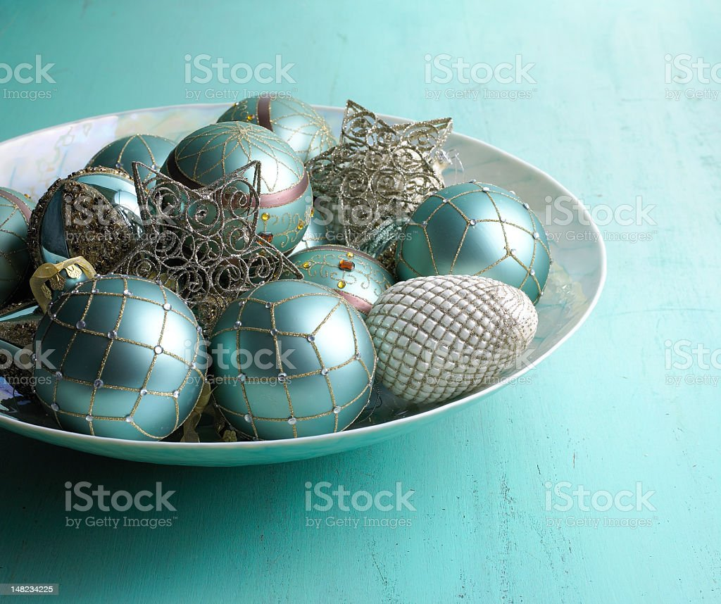 A blue table with a bowl of blue Christmas ornaments stock photo