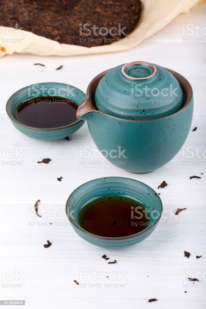 Blue teapot and two small cups full of puer tea on white table. Pressed Chinese fermented Pu-erh tea. stock photo