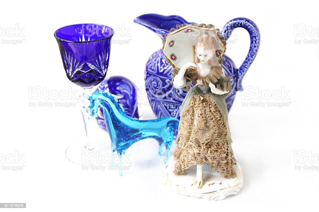 Blue theme glass knick knacks with antique ceramic figurine stock photo