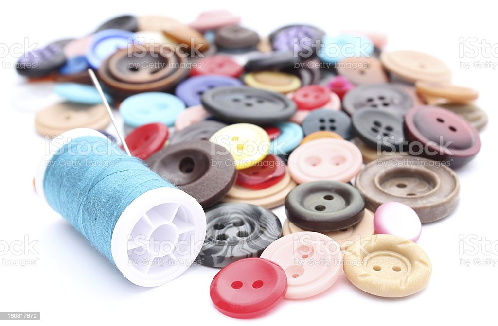 Blue thread with needle and collection of colored sewing buttons royalty-free stock photo