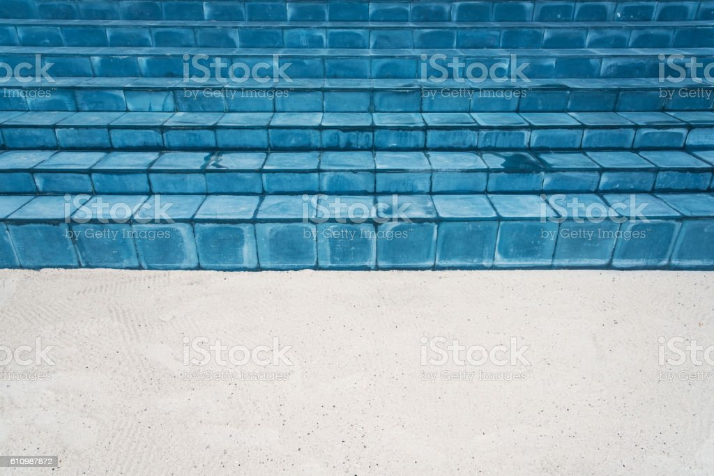 Blue tiled floor stairs and beach sand stock photo
