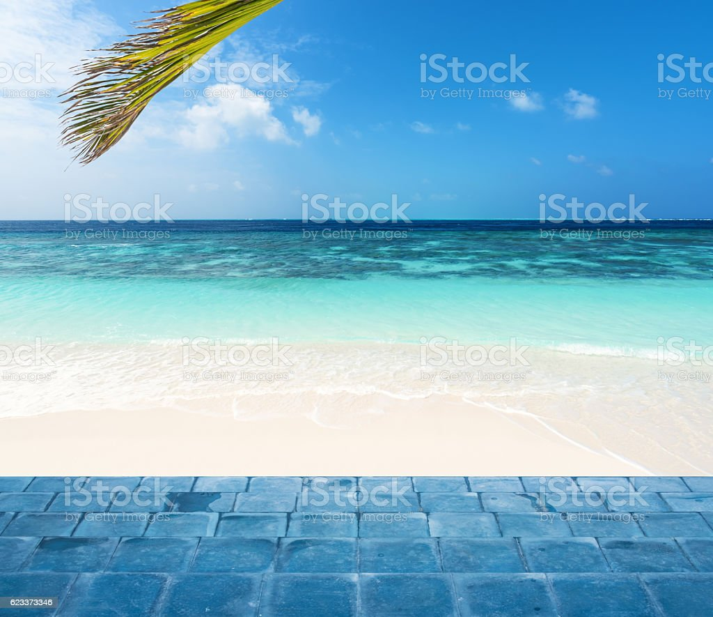 Blue tiled floor stairs into tropical beach stock photo