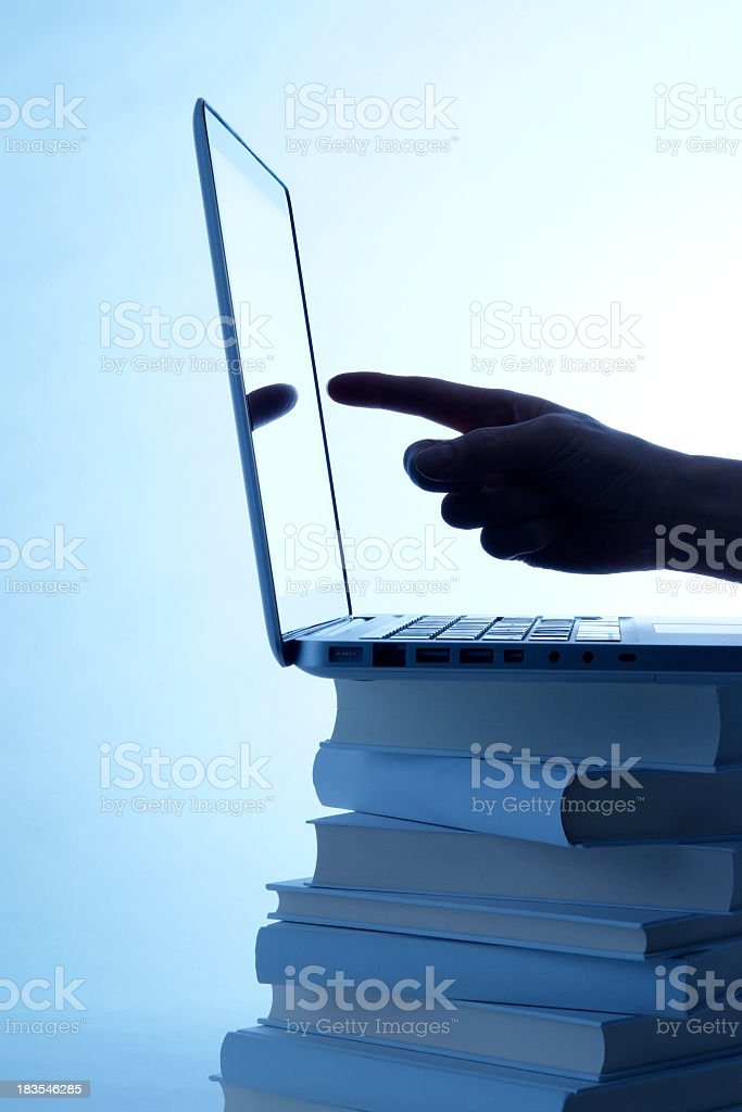 Blue tinted image of laptop and pointing finger on book royalty-free stock photo