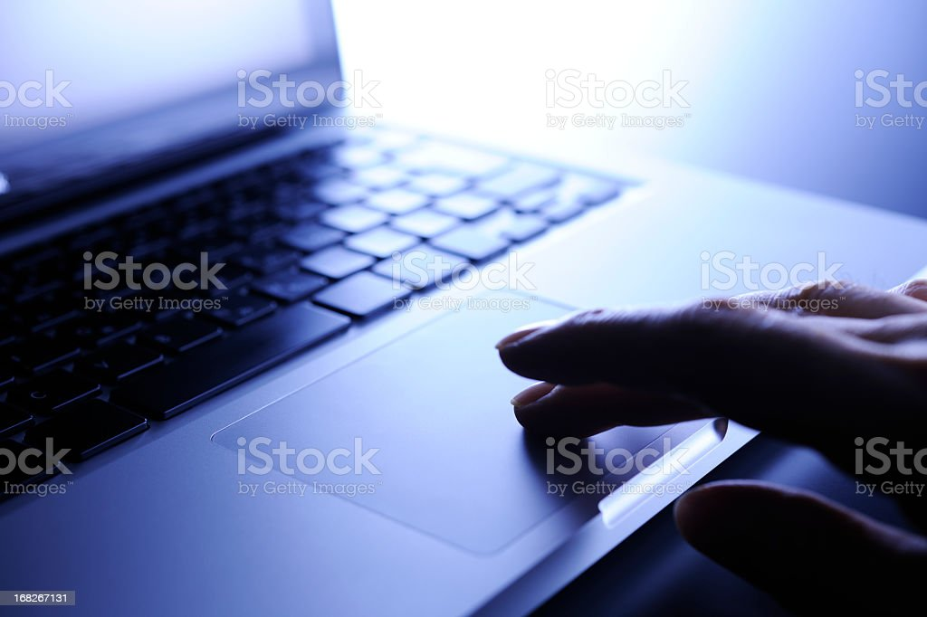 Blue tinted image of laptop computer work, finger on touchpad stock photo