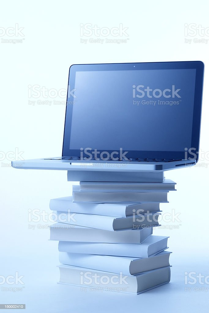 Blue tinted image of laptop on the stacked blank books royalty-free stock photo