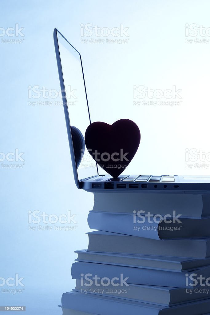 Blue tinted image of laptop with heart shape on books stock photo