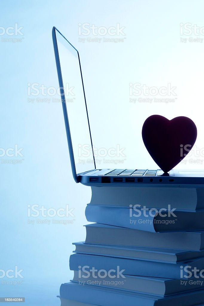 Blue tinted image of laptop with heart shape on books royalty-free stock photo