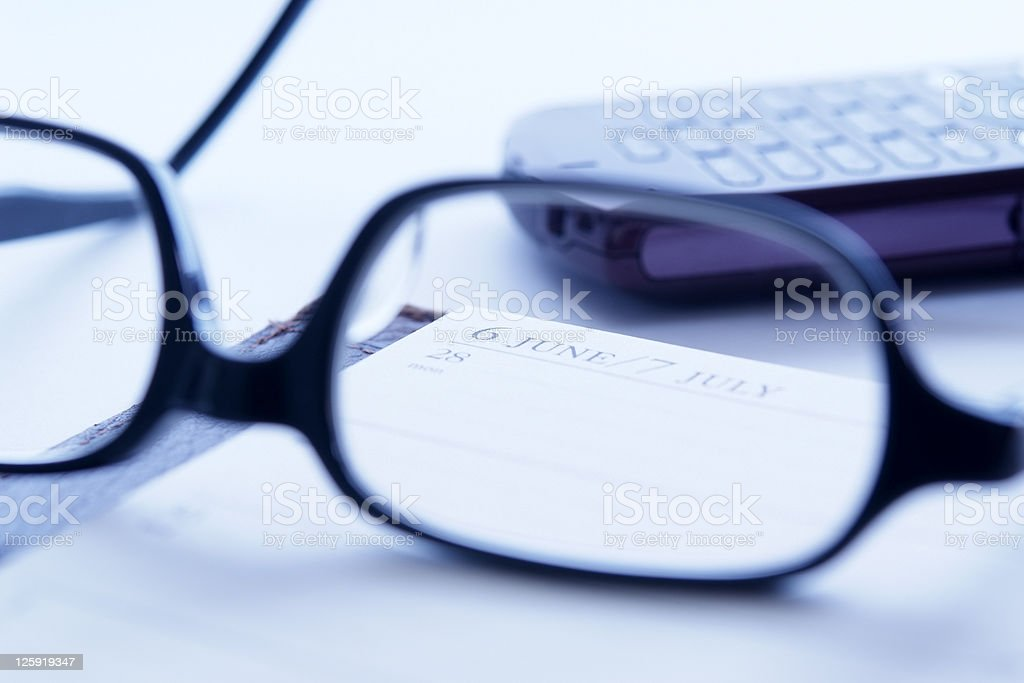Blue tinted image of opened personal organizer with glasses royalty-free stock photo