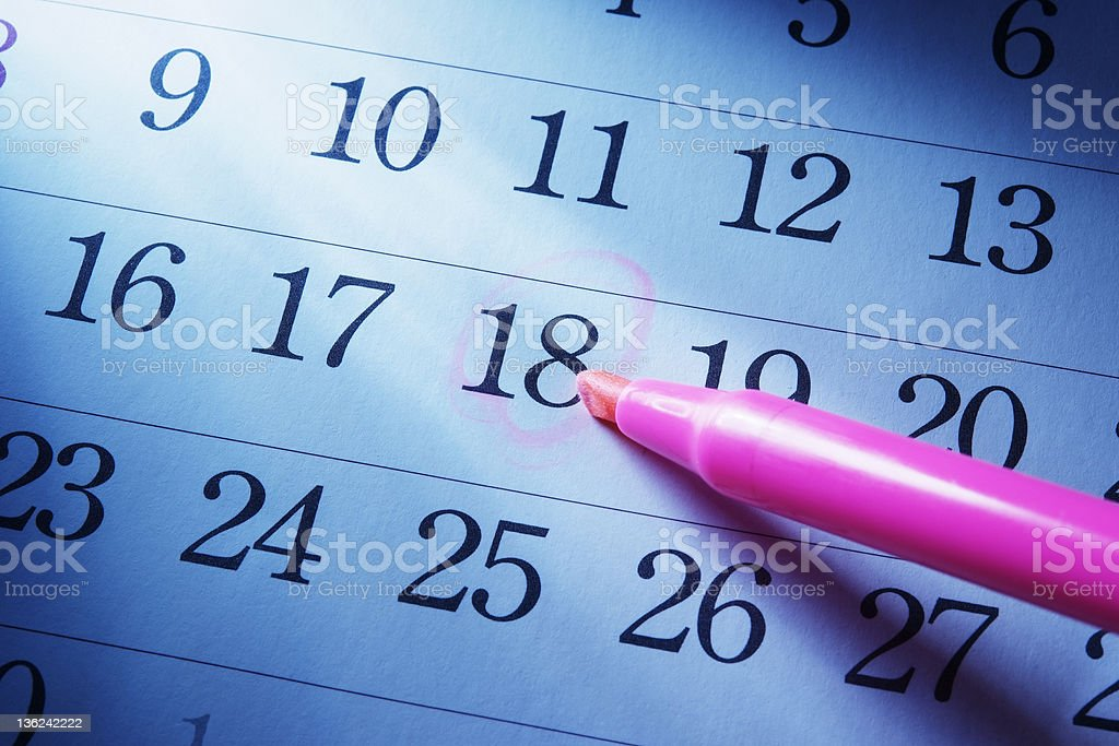 Blue tinted image of setting a date on calendar royalty-free stock photo