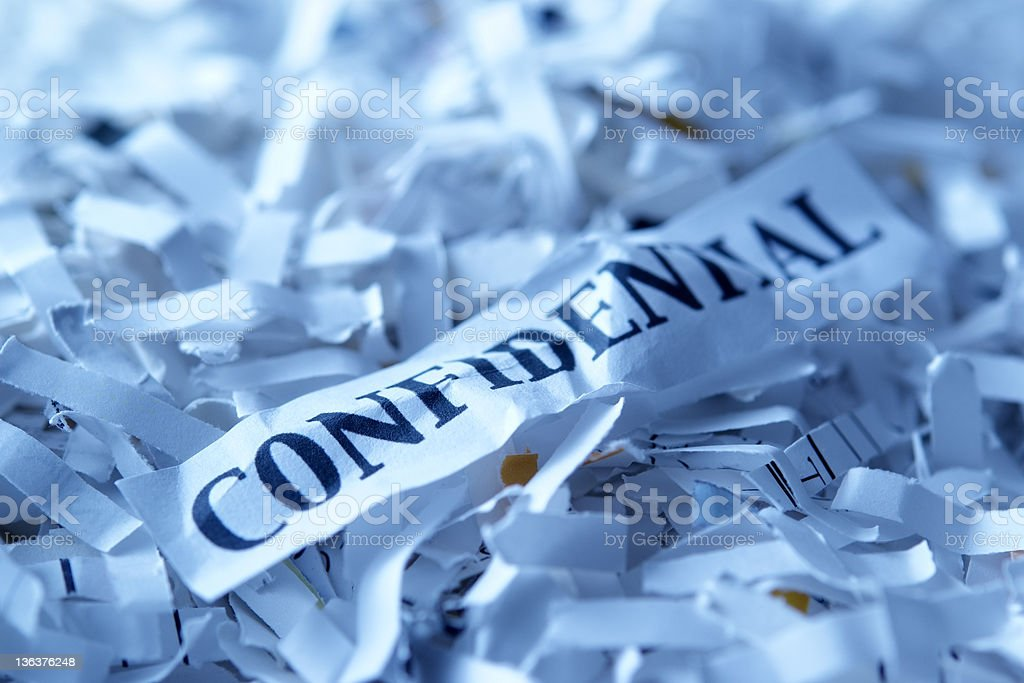 Blue tinted image of shredded confidential documents royalty-free stock photo