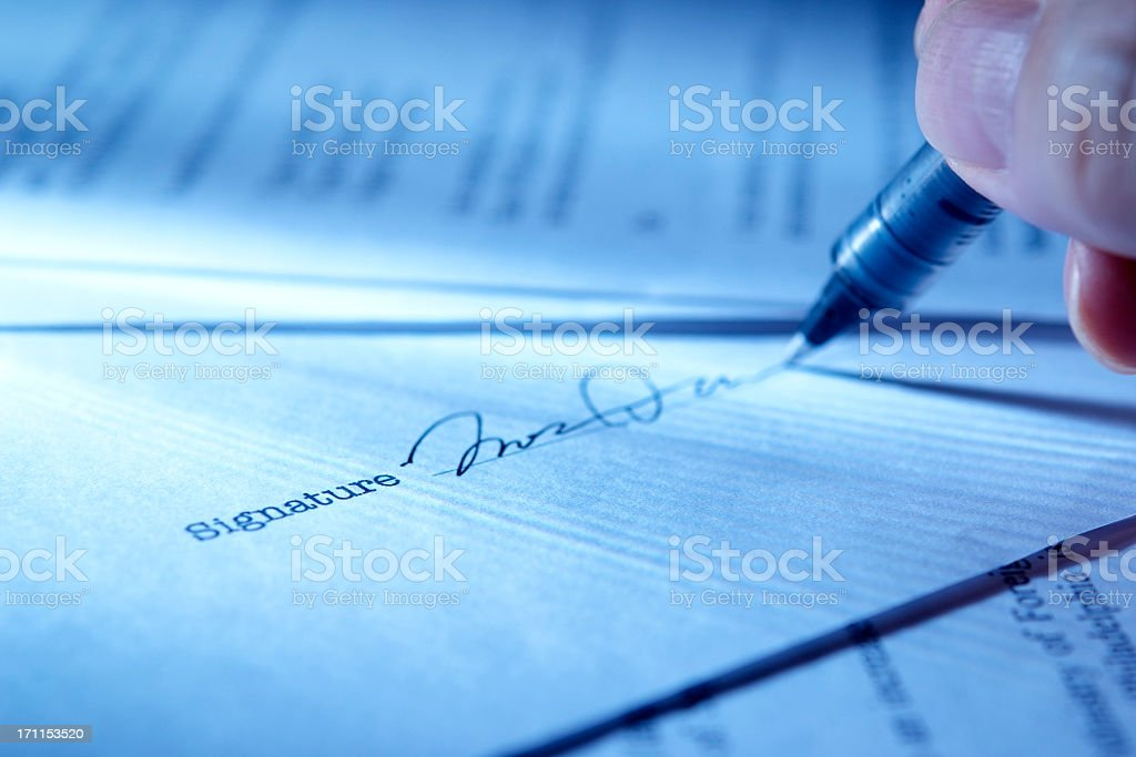 Blue tinted image of signing a contract with light rays royalty-free stock photo
