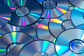 Blue tinted image of stacked CD/DVD texture background